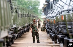 FILE - A Cambodian army soldier looks at Chinese military vehicles displayed before a handover ceremony at a military airbase in Phnom Penh, Cambodia, Wednesday, June 23, 2010.