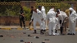 Forensic policemen inspect the site of a suicide bomb attack at a parade square in Sanaa, Yemen, May 21, 2012.