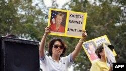 Người biểu tình thuộc phe bảo hoàng giơ cao những tấm bảng kêu gọi đại sứ Mỹ tại Thái Lan hãy im đi, 16/12/2011