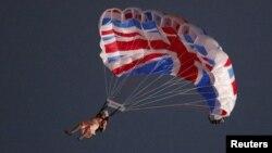 Penerjun payung Gary Connery melakukan terjun dari helikopter dengan parasut berhiaskan bendera Inggris. Connery mengenakan pakaian sama seperti pakaian Ratu Elizabeth lengkap dengan rambut 'wig' (27/7).