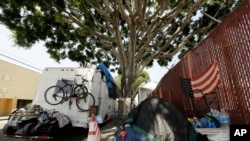 FILE - A RV vehicle is parked next to a tent on the streets in an industrial area of Los Angeles, Wednesday, July 31, 2019. (AP Photo/Damian Dovarganes)