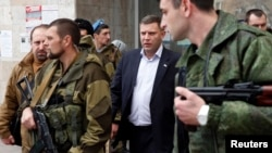FILE - Head of the self-proclaimed Donetsk people's republic Alexander Zakharchenko (C) is seen surrounded by bodyguards in Donetsk, eastern Ukraine, Nov. 14, 2014.