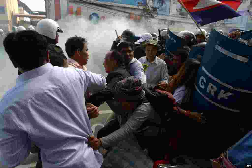 Mam Sonando (C), owner of the independent Beehive radio station and prominent government critic, and other activists run as military police officers (R) disperse the crowd during a protest in Phnom Penh, Cambodia.