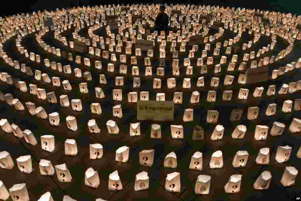 A Kosovo boy sits in the middle of a circle of lit candles to commemorate those who went missing during 1998-99 Kosovo war, in Pristina, Kosovo, Apr. 26, 2013.
