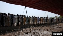 FILE - Men fleeing from the military offensive against Pakistani militants in North Waziristan queue to get relief handouts from a storage tent of the World Food Program at a distribution point for internally displaced persons in Bannu, located in Pakistan's Khyber-Pakhtunkhwa province, July 6, 2014.