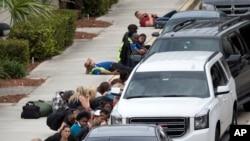 فائرنگ کی آواز سن کر لوگ گاڑیوں کے پیچھے چھپ گئے۔
