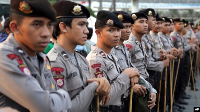 FILE - Indonesian police stand guard ahead of a planned protest at a major intersection in Jakarta, July 22, 2014.