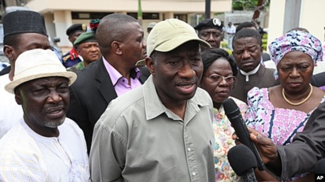 Nigeria President Goodluck Jonathan, center, speak to journalists, August 27, 2011 after visiting the explosion site at the United Nation's office in Abuja, Nigeria