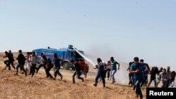 Para demonstran berlari menghindari semprotan meriam air dari kendaraan tentara yang berupaya membubarkan mereka di kota Suruc, provinsi Sanliurfa (7/10).