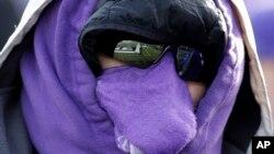 Un aficionado de fútbol americano universitario se envuelve completamente en sus colores para protegerse del frío en Oklahoma.