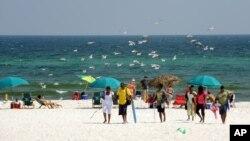 FILE- Beach goers enjoy Pensacola Beach in Pensacola, Florida, July 11, 2010.
