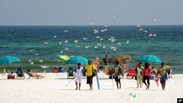 FILE- Beach goers enjoy Pensacola Beach in Pensacola, Florida, July 11, 2010.