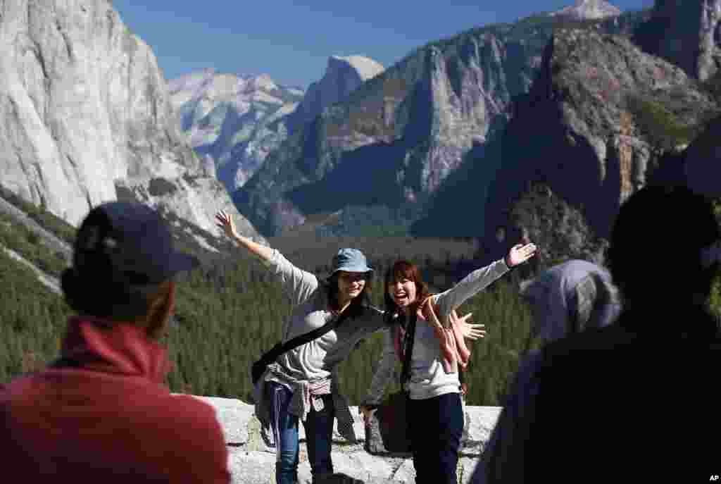 Visitors at Tunnel View, like Kaori Nishimura and Eriko Kuboi from Japan, pose in front of Half Dome, center facing, during the reopening of Yosemite National Park, Calif., Oct. 17, 2013.