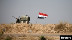 A military vehicle of the Iraqi security forces is seen next to an Iraqi flag in Fallujah, Iraq, June 13, 2016. An operation to liberate the city from Islamic State militants is now in its third week.
