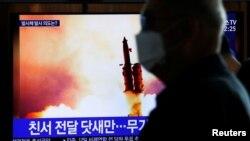 Seorang pria melintas di depan layar TV di Seoul, Korea Selatan, yang menyiarkan berita Korea Utara menembakkan proyektil, Senin, 9 Maret 2020. (Foto: Reuters)