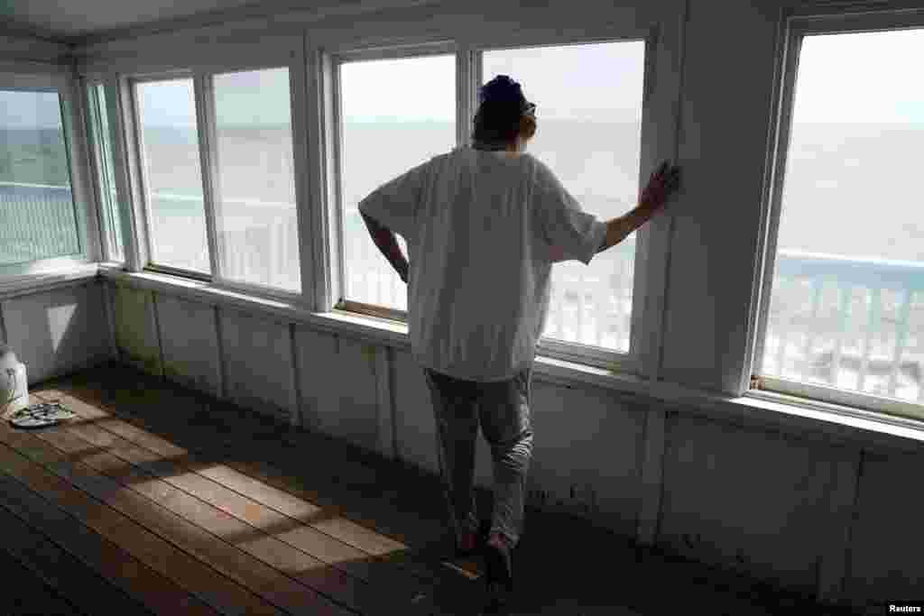 A woman, who refused to give her name, looks out over the water from her porch amid fears she will never see her home again as Hurricane Michael bears down on Alligator Point, Florida, Oct. 9, 2018.
