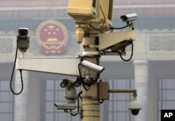 A pole attached with security cameras to monitor Tiananmen Square stands against a backdrop of the Chinese Communist Party emblem on the Great Hall of the People in Beijing, Oct. 20, 2014.