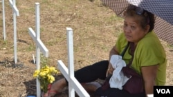 A woman remembers her loved one at the mass-burial site marked with 3,000 crosses for the people who perished when super typhoon Haiyan smashed through Tacloban City and the central Philippines. Holy Cross Memorial Park, Tacloban. Nov. 8, 2014. (Simone Orenain/VOA)