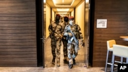 Junta soldiers walk through a hotel during a meeting with high level representatives from the Economic Community of West African States (ECOWAS), in Conakry, Guinea, Sept. 17, 2021.
