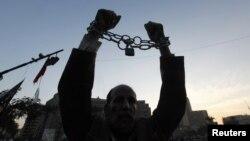18일 이집트 카이로 타흐리르 광장에서 열린 시위에서 헌법 초안에 반대하는 의미로 사슬에 묶인 손을 들어보이는 시위대.