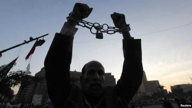 A man holds up his chained hands as he protests against Egypt's President Mohamed Morsi at Tahrir Square in Cairo, Egypt, December 18, 2012.