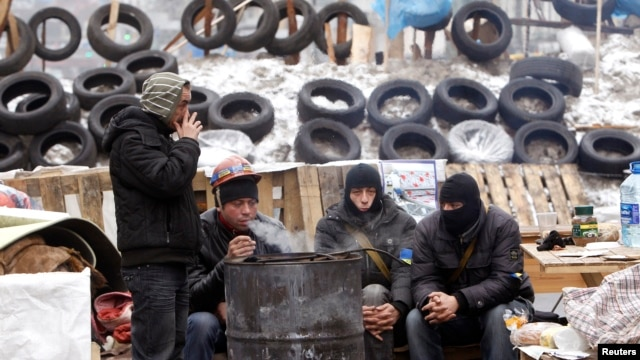 Pro-European protesters warm themselves at a fire in front of barricade in central Kyiv, Dec. 16, 2013.