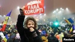 یک معترض در جمع مردم کاغذی دارد که روی آن به زبان رومانی نوشته شده «دولت بدون فساد».