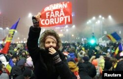"FILE - A woman holds up a sign that reads ""Government without corruption"" during a demonstration of thousands of Romanians against their government in Bucharest, Feb. 6, 2017."