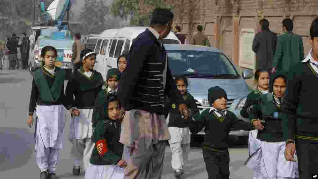 مامور امنيتی لباس شخصی دانش آموزان را از مدرسه مورد حمله طالبان قرار گرفته به جای امنی هدايت می کند-- ۲۵ آذر (۱۶ دسامبر)