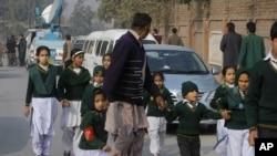 Yon polisye an inifòm ap akonpaye yon gwoup elèv ki sòti nan lekòl Taliban yo atake nan vil Peshawar, nan Pakistan. (Foto: Madi 16 desanm 2014).