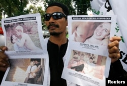 FILE - A member of the Islamic Defenders Front (FPI) holds up posters protesting against films in Jakarta, Sep. 28, 2010. The gay and lesbian community in Indonesia faces discrimination.