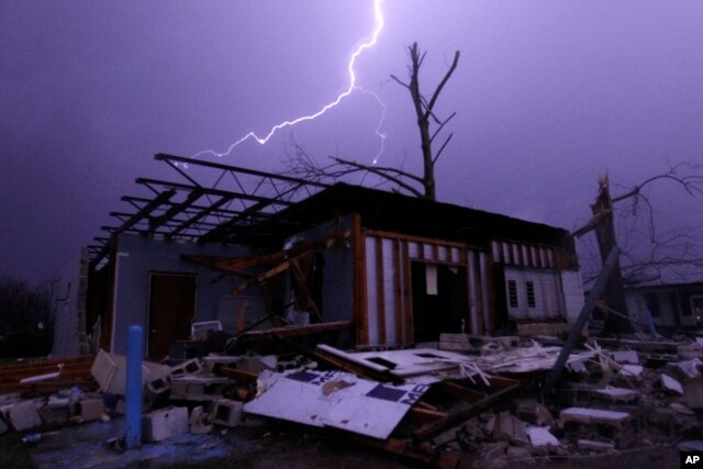 FILE - Lightning illuminates a house after a tornado touched down in Jefferson County, Ala., damaging several houses in Birmingham, Dec. 25, 2015.