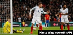 England's Jamie Vardy, center, and Raheem Sterling, right, celebrate after Vardy scored his side's second goal passing Spain's goalkeeper Jose Reina, left, during the international friendly soccer match between England and Spain at the Wembley stadium.