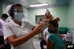 Seorang perawat bersiap menyuntik vaksinasi seorang tenaga kesehatan dengan dosis kedua kandidat vaksin COVID-19 Kuba, Abdala, di Cienfuegos, Kuba, 30 Mei 2021. (Foto: Yamil LAGE / AFP)