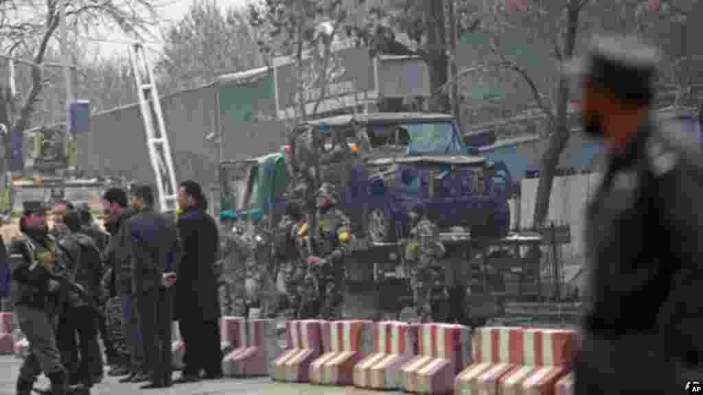 Turkish and Afghan security personal inspect a damaged vehicle at the site of a suicide attack in Kabul, Feb. 26, 2015.