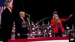 FILE - In this Dec. 5, 2020, file photo Sen. Kelly Loeffler, R-Ga., speaks as President Donald Trump and Sen. David Perdue, R-Ga., listen at a campaign rally at Valdosta Regional Airport, Dec. 5, 2020, in Valdosta, Georgia.