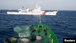 Sebuah kapal China (atas) tampak berlayar dekat kapal AL Vietnam di Laut China Selatan (foto: ilustrasi).