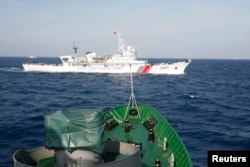 FILE - A Chinese Coast Guard ship (top) is seen near a Vietnam Marine Guard vessel in the South China Sea, about 210 km (130 miles) off shore of Vietnam, May 14, 2014.