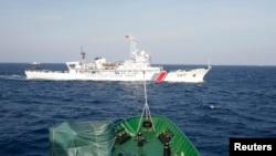 2014年5月14日, 在越南海岸外大约210公里海域,从越南巡逻船上看到的中国海警船。越南船只靠近中国在有争议水域部署的一座石油钻井平台时,会遭到中国船只抵近拦阻。