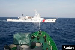 FILE - A ship (top) of Chinese Coast Guard is seen near a ship of Vietnam Marine Guard in the South China Sea, about 210 km (130 miles) off shore of Vietnam, May 14, 2014.