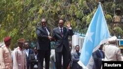 Le nouveau président somalien élu Mohamed Abdullahi Mohamed (à droite) marche aux côtés de l'ancien président Hassan Sheikh Mohamud (à gauche) lors d'une cérémonie au Palais présidentielle à Mogadiscio, le 16 février 2017