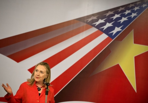 U.S. Secretary of State Hillary Clinton speaks in front of U.S. flag and Vietnamese flag.