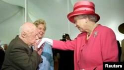 FILE: Actor Mickey Rooney (L) kisses the hand of Britain's Queen Elizabeth II during a garden party celebrating her state visit to the U.S. at the British Embassy in Washington, May 7, 2007.