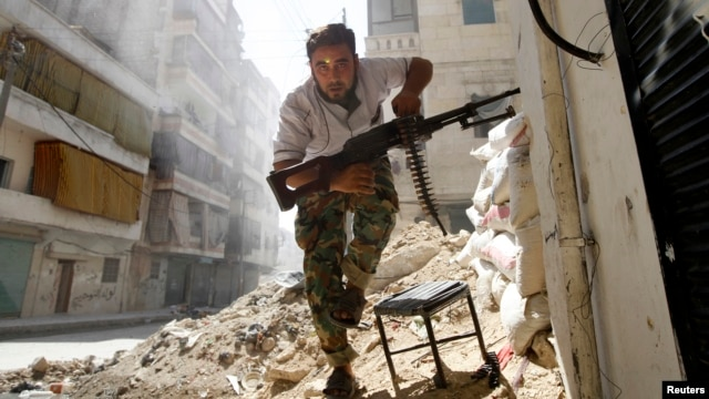 A Free Syrian Army fighter takes cover during clashes with Syrian Army in central Aleppo in this August 7, 2012 photo.