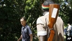 An armed youth mans the gates of a farm which was seized from white farmers in Chegutu in 2010 (File).