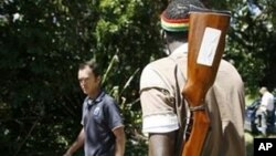 FILE: An armed youth mans the gates of a farm which they seized from white farmers in Chegutu 120km south west of Harare.