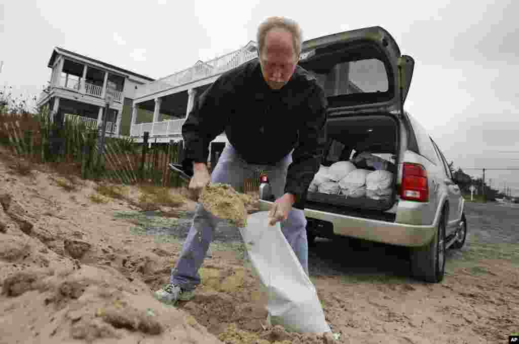 Mike Strobel fills sand bags for his business, Mike's Carpet Connection, as Hurricane Sandy bears down on the East Coast, Sunday, Oct. 28, 2012, in Fenwick Island, Delaware.