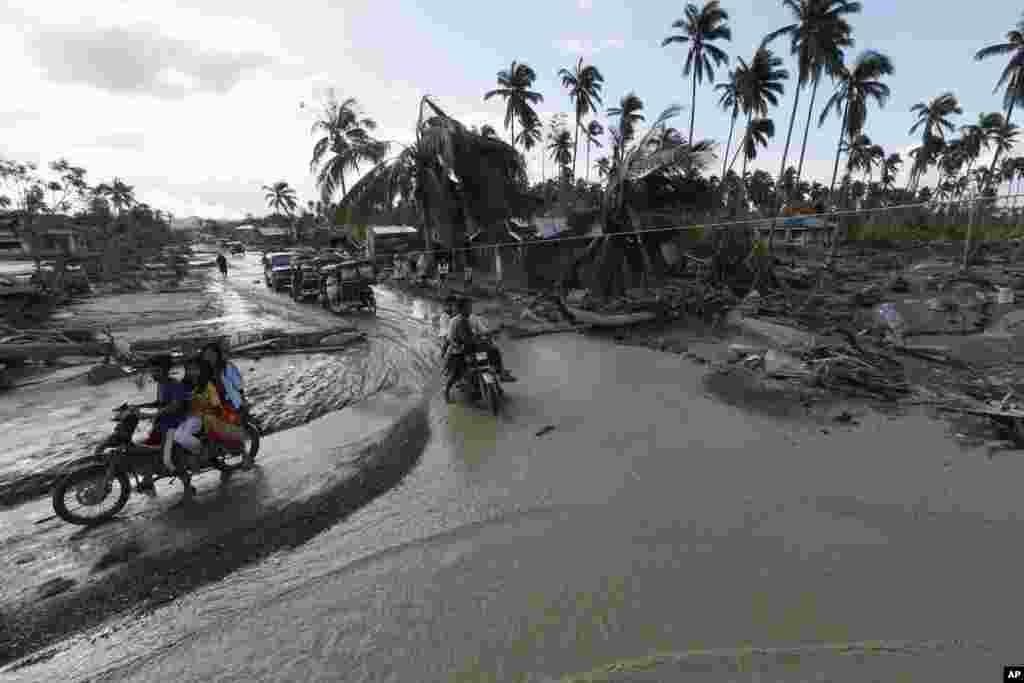 Residents make their way through a flooded area of New Bataan township, Compostela Valley in southern Philippines, December 5, 2012, a day after Typhoon Bopha made landfall.