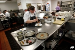 """In this Dec. 7, 2012 photo, executive chef Kristin Butterworth prepares a """"reveillon"""" meal at the Grill Room of the Windsor Court Hotel in New Orleans."""