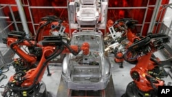 Kuka robots work on Tesla Model S cars in the Tesla factory in Fremont, Calif., Thursday, May 14, 2015. (AP Photo/Jeff Chiu)